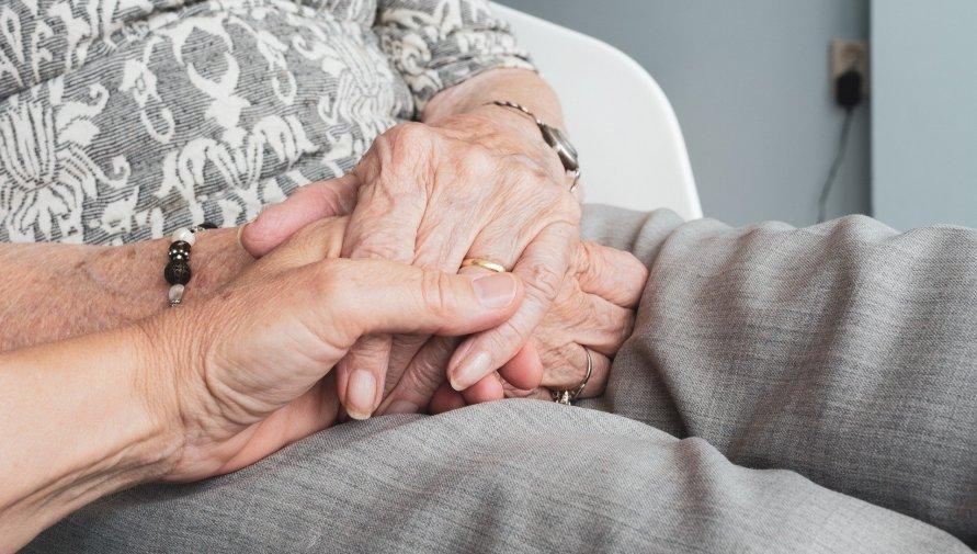 Ręce starszej osoby trzymane przed młodszą dłoń na kolanach w szarych spodniach