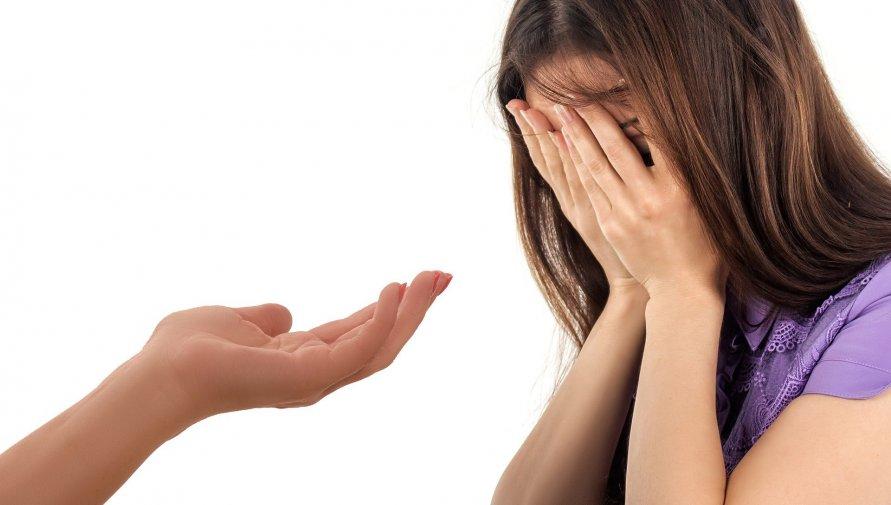 Kobieta z zakrytą rękami twarzą i wyciągnięta do niej dłoń