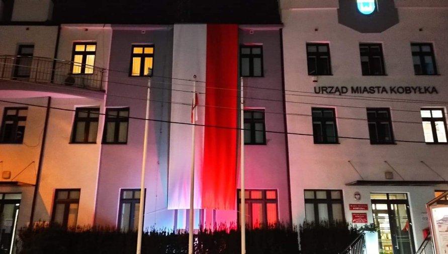 Budynek Urzędu Miasta z flagą i podświetlony na biało-czerwono