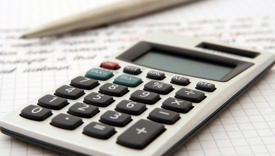 Na zdjęciu kalkulator i długopis na tle zapisanej kartki.