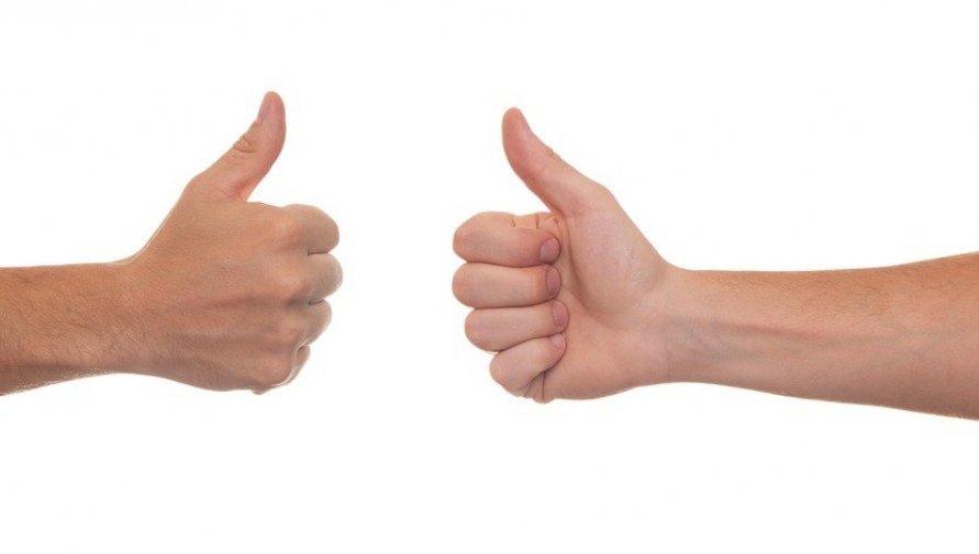 Dwie ręce z uniesionymi kciukami na białym tle
