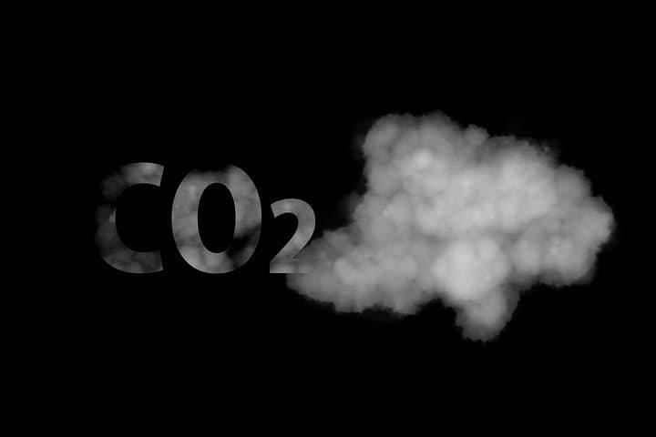 Czarne tło, na nim szary dym i szare litery CO2