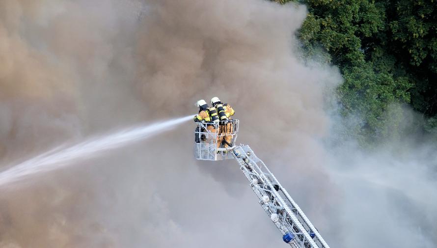 strażacy na wysięgniku gaszący palący się las