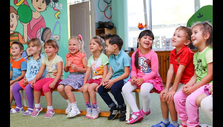 Zdjęcie dzieci  siedzących na ławeczce w sali przedszkolnej