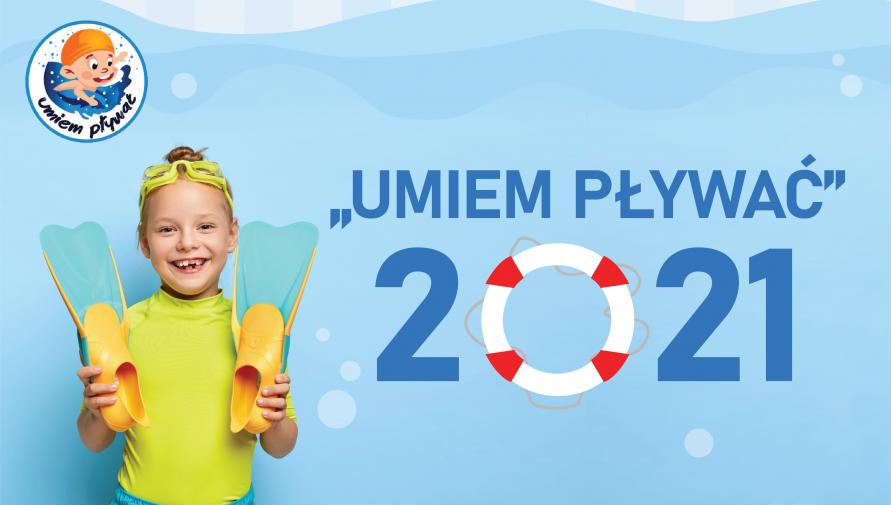 uśmiechnięta dziewczynka w stroju kąpielowym trzymająca płetwy do pływania, napis umiem pływać 2021