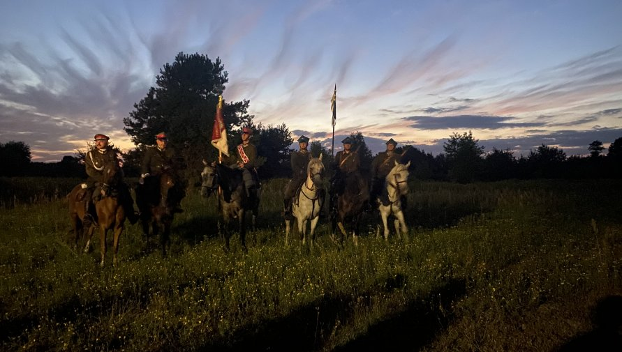 Na trawie stoi pięć koni z jeźdźcami, w tle zachmurzone niebo