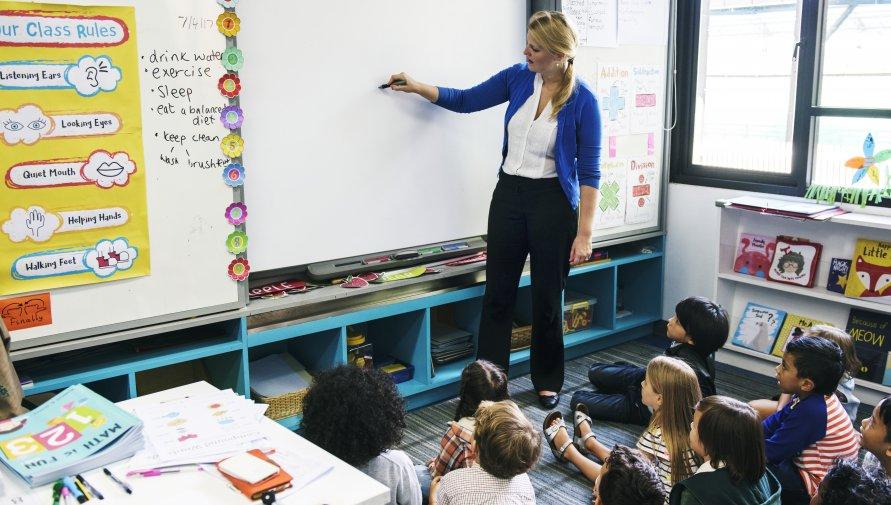 lekcja, dzieci siedzące na podłodze po turecku, nauczycielka pisząca coś na tablicy